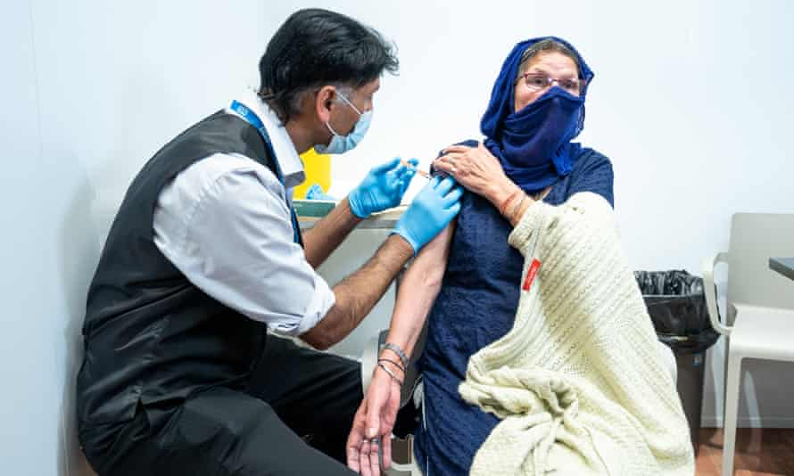 Doctor vaccinating woman with headscarf