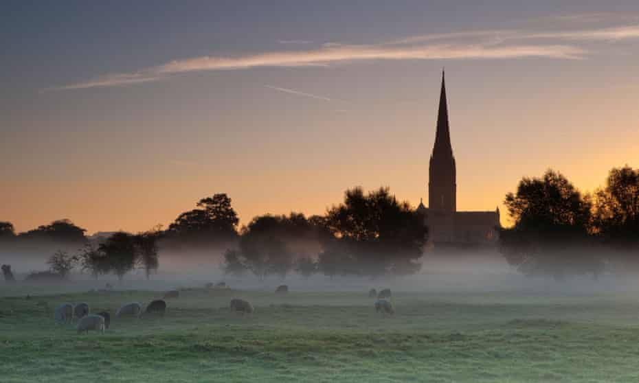 Salisbury Cathedral at sunrise as mist hangs over a meadow of sheep