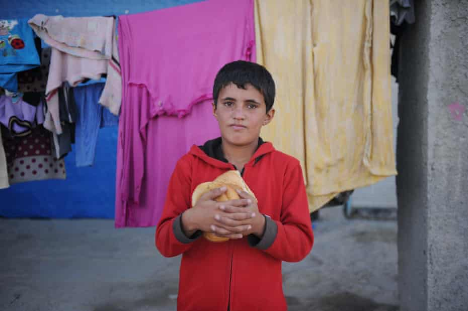 A Kurdish refugee boy from the Syrian town of Kobani carries loaves of breads to his family tent for breakfast in a camp in the south-eastern town of Suruc
