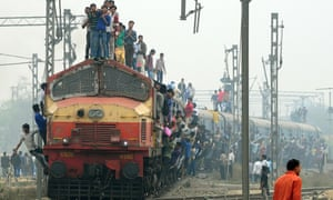 Passengers stand and hang onto a train as it departs New Delhi. The government is spending a record $2.6bn on new trains.
