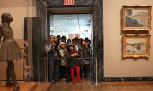 Tourists watch crews hang a Renoir at the Museum of Fine Arts in Boston in 2015.