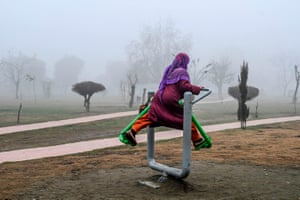 A woman exercises in a city park on a foggy morning in Srinagar, India