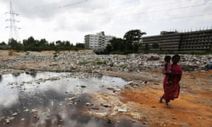 An woman walks past contaminated water at a landfill on the outskirts of Bangalore in 2015.