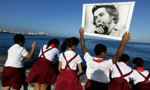 Students carry a photograph of Che Guevara at Havana's seafront Malecón.