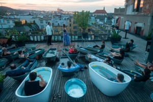 Spectators in bathtubs listen Czech opera singers Adam Plachetka and Eva Kyvalova performing parts of Mozart's Don Giovanni, at the rooftop of Lucerna Palace building in Prague