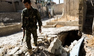 A YPG fighter walks near the entrance of a tunnel used by ISIS militants to avoid detection while moving between their positions.