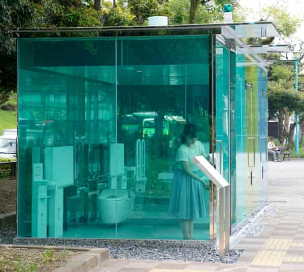 An employee of the Nippon Foundation demonstrates a public toilet designed by Shigeru Ban