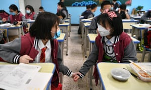 Students wearing face masks chat in a classroom in Kunming, Yunnan Province of China. Many schools around China have reopened.