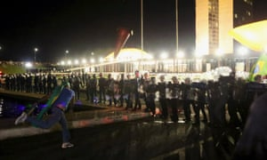 A demonstrator throws a cone against police officers during a protest in Brasilia.