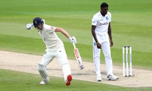 England's Dom Sibley celebrates his century as West Indies' Alzarri Joseph looks on.