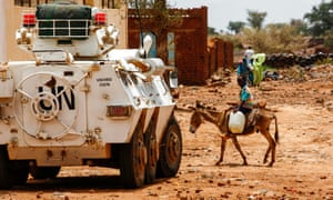 A Sudanese boy rides a donkey past a Unamid armoured vehicle in Darfur