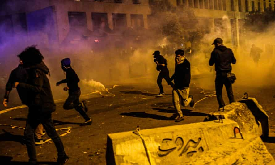 Protesters flee tear gas in clashes with security forces in Beirut on Saturday.