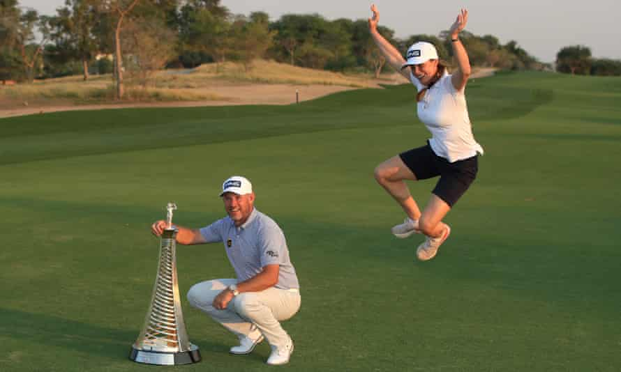 Lee Westwood's girlfriend and caddie, Helen Storey, joins in the celebrations as he poses with the Race to Dubai trophy
