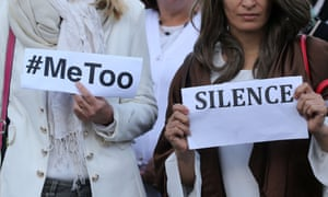 Women hold signs at a #MeToo demonstration