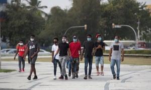 Young people wearing masks walk through Santo Domingo, Dominican Republic, 22 June, 2020.