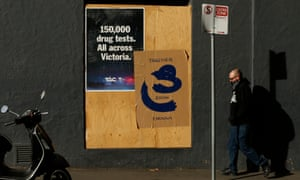 A man walks past a boarded up hotel in Melbourne, Australia