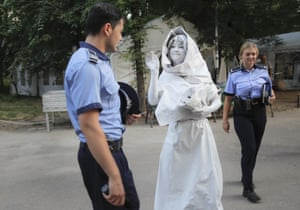 An Artel Myth artist passes Romanian police officers before performing as her Concordia character