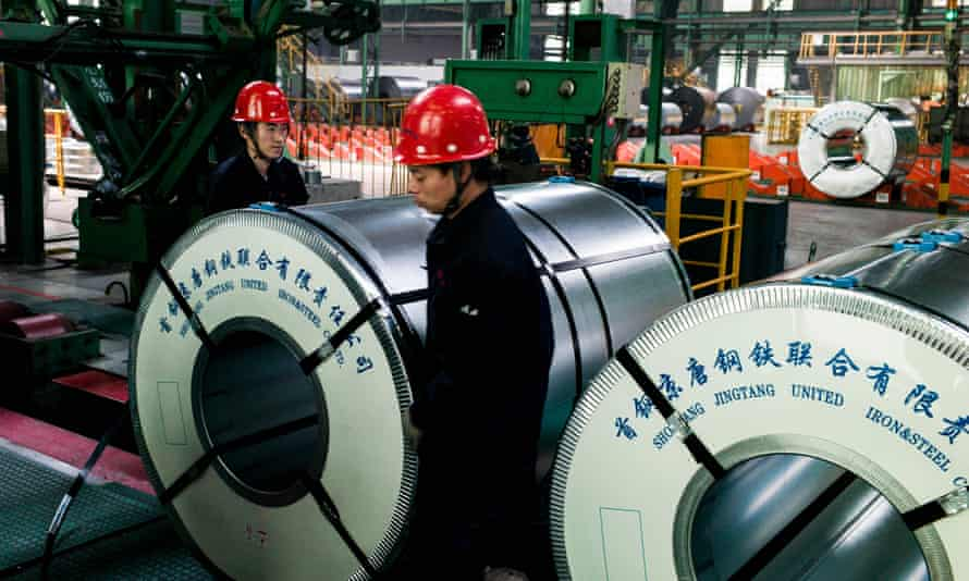 Chinese workers pack steel rolls in a factory in Hebei province
