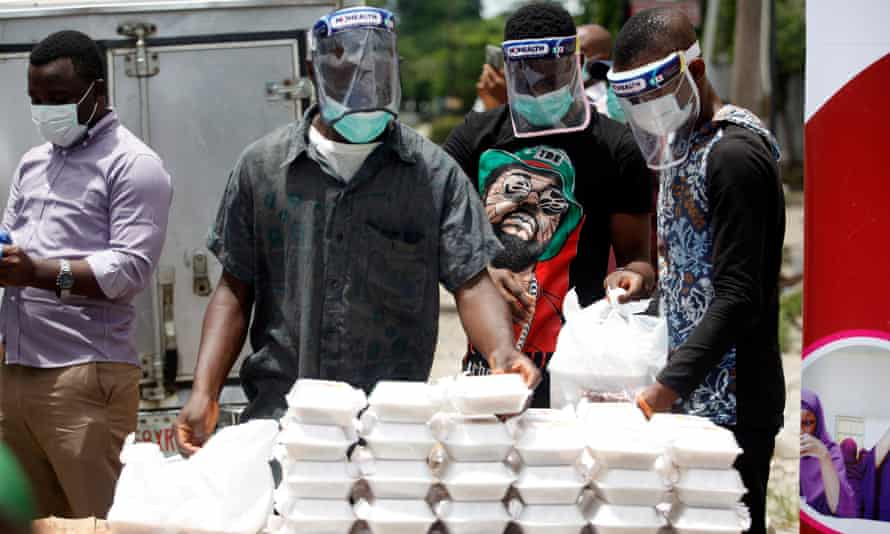 Volunteers wearing face shields distribute food in Lagos, Nigeria, where improving the level of testing has been difficult.