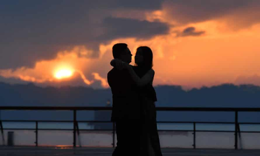silhouette of a couple hugging against a sunset