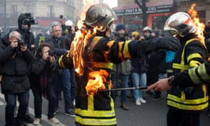 Firefighters simulate setting themselves on fire during the protest in Paris