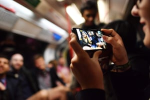 A commuter takes a picture of people as they take part in the annual 'No Trousers On The Tube Day' (No Pants Subway Ride) on the Central line in London