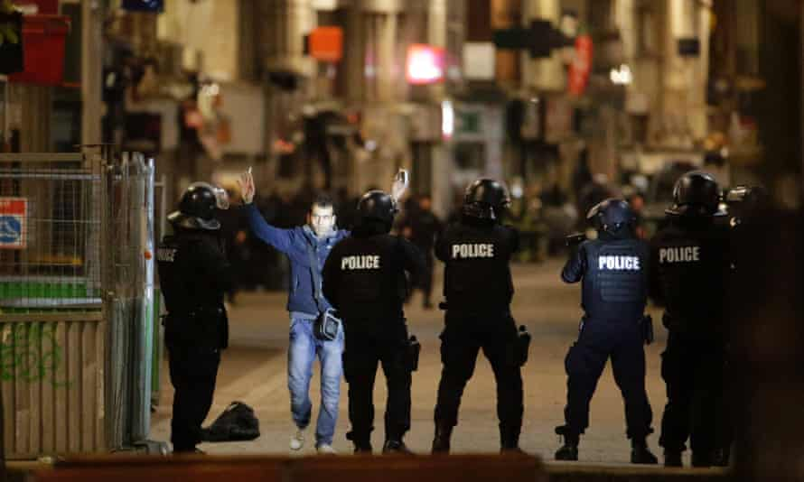 A man raises his arms to French police in the Paris suburb of Saint-Denis during the manhunt for the surviving terrorists who killed 129 people in November.