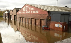 An abandoned car is pictured in flood water surrounding buildings in Rotherham.