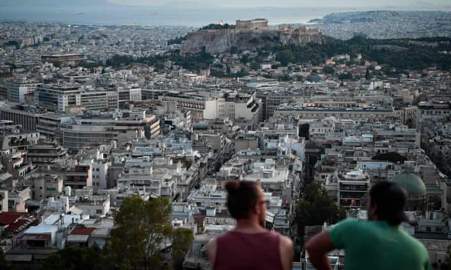 Two young men sit on a hill overlooking Athens.