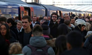 Commuters disembark a South Western Railway train at Waterloo Station