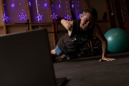 Jason Whiter doing a one-armed push up in front of his laptop. In the background, his home gym is hung with purple, star-shaped fairy lights.