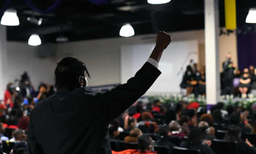 A person raises their fist during the funeral for Daunte Wright.
