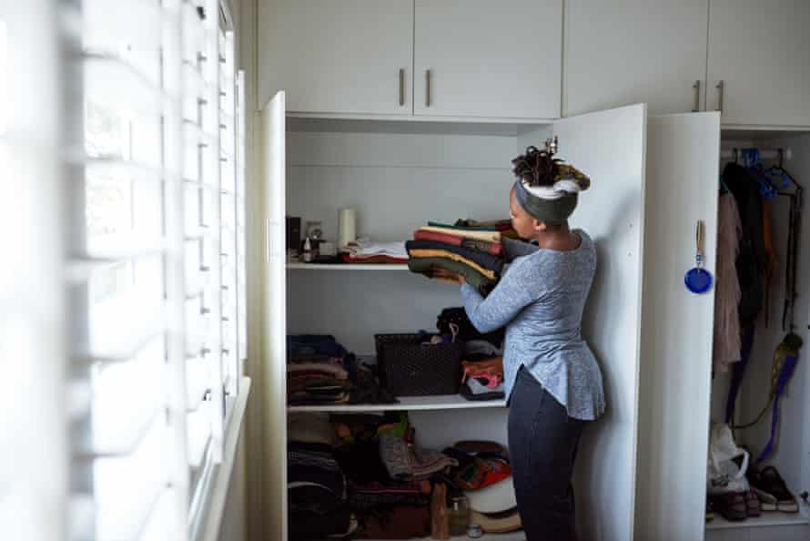 A woman carefully putting away neatly folded clothes