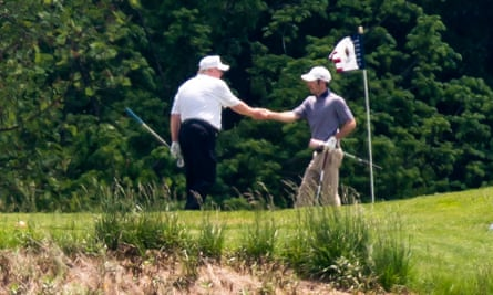 Donald Trump shakes hands during a round of golf on Saturday.