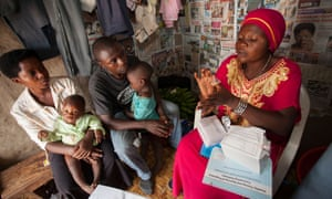 A community health volunteer explains how to use a condom to a young family in Kasese, Uganda