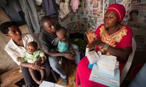 A community reproductive health volunteer gives contraceptive advice to a young family in Kasese, Uganda