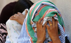 Asylum seekers sent back by Australia cover their faces outside court in Sri Lanka