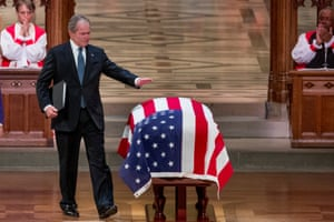 George W Bush touches the flag-draped casket of his father