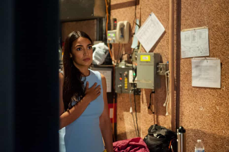 Alexandria Ocasio-Cortez stands for the National Anthem backstage.