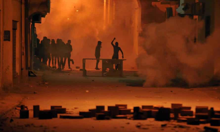 Protesters clash with Tunisian security forces in Tebourba on Wednesday.
