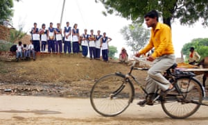 A man cycles in Atta Gujran, outside New Delhi, as school girls wait for the bus