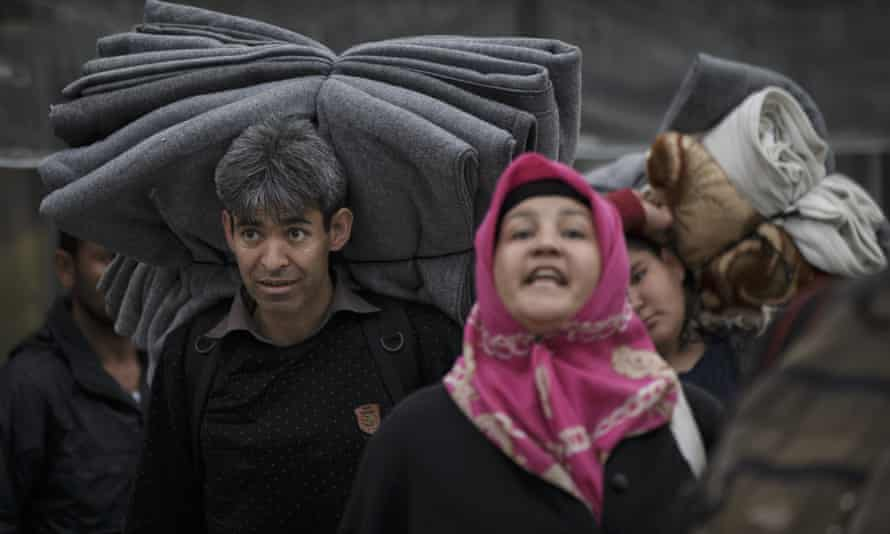 Migrants carry belongings, in Athens' Victoria Square.