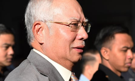 Malaysia's former prime minister Najib Razak is escorted by police to the courthouse in Kuala Lumpur on Thursday to face fresh 1MDB charges.