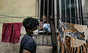 Wearing a facemask, Ricardo Fernandes, 30, takes parcels of necessities around the City of God favela