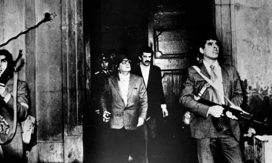 Armed guards watch for attackers as Chilean president Salvador Allende leaves a building during the military coup in which he was overthrown.