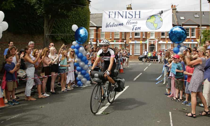 Tom Davies on bike under Finish banner