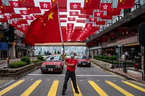 A party supporter waves a Chinese flag under hundreds of flags on a Hong Kong street
