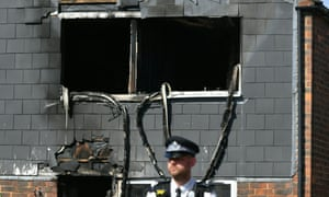 A police officer in front of a house after a fire in Deptford, London