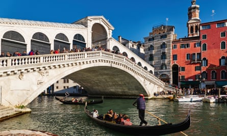 Tourists throng the Rialto bridge in summer.