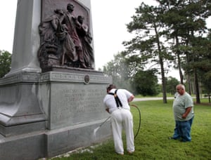 St Louis parks workers clean a Confederate memorial after it was spray painted with 'black lives matter'